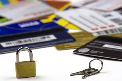 Lots of scattered different credit cards. A small padlock and the keys to it. Lots of scattered credit cards. A small padlock and the keys to it royalty free stock image