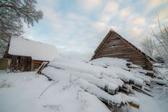 Lots of snow covered wooden houses. In Lithuanian village Silenai stock images