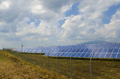Lots of solar panels behind rusty barbed wire. In the field near Sofia Stock Photo