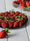 Lots of strawberries in a still life on a white background, summer garden wooden white table royalty free stock photo
