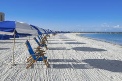 Lots of sun loungers and beach umbrellas. On silver sand,  vacation concept Stock Photography