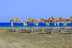 Lots of sun protection umbrellas on the beach close to Pervolia. Lots of sun protection umbrellas blown by the wind on the beach close to Pervolia in Cyprus the Stock Image