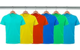Lots of T-shirts on hangers isolated on white Stock Image