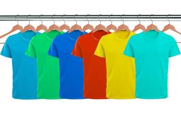Lots of T-shirts on hangers isolated on white royalty free stock photography