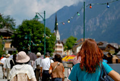 Lots of Tourists. In Hallstatt, a village in Austria, with a redhaired woman in foreground Royalty Free Stock Image