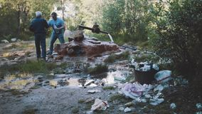 Lots of trash in front of metal pipe wellspring on forest mountain trail. Sunny day. Men filling bottles. Refugee concept, society or ecology problems stock video