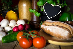 A lots of vegetables and bread on a wooden table, heart with cop Stock Images