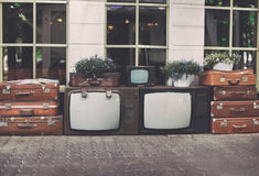 Lots vintage tv set with old retro suitcases and house plants in pots for decoration inspiration on street stock images
