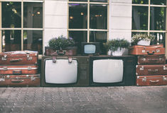Lots vintage tv set with old retro suitcases and house plants in pots for decoration inspiration on street. Lots vintage tv set with old retro suitcases and Stock Image