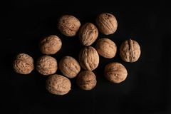 Lots of walnuts on black background and Nutcracker. Halves of nuts.  stock photos