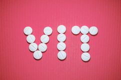 Lots of white smooth convex tablets with dividing strip on pink striped background, in the form of word VIT, vitamins. Lots of white smooth convex tablets with stock photo