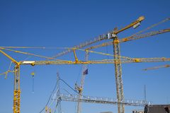 Lots of yellow cranes against a deep blue sky. Almost abstract composition with copy space. Stock photo stock photo