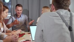 Team working on business ideas. Lots of young and ambitious business people sitting in the office and sharing ideas. Successful meeting: Man giving his friend stock footage