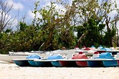 Lott av det färgrika pedalfartyget på stranden royaltyfri foto