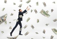 Lott av det kontanta den pengarflyget och affärsmannen som fångar dem royaltyfria foton