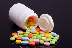Lott av färgrika preventivpillerar med den vita asken på svart bakgrund Royaltyfri Bild
