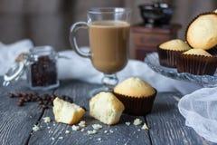 Lott av hela muffin och stycken på trätabellen, bredvid den glass koppen med cappuccino royaltyfria foton