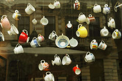 Lott av kaffekoppar som hänger på trådar med en byggnadsreflexion i baksidan Royaltyfri Bild