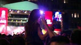 Lott av ljusa ljus och illuminationsenheter på platsen, härligt flickasammanträde på skuldror av grabben, etappljus, lott av barn lager videofilmer
