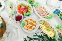 Lott av olika köttmellanmål på den rika lyxiga sköta om tabellen Royaltyfri Fotografi