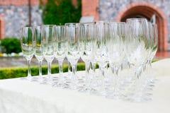 Lott av tomma vinexponeringsglas på buffétabellen som är förberedd för utomhus- partier Fotografering för Bildbyråer