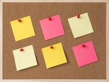 Lott en guling, rosa stickry anmärkning på träramkorkbräde royaltyfri bild