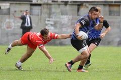 Lotta dei giocatori di rugby per la palla Fotografie Stock