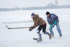 Lotta del giovane con l'uomo anziano per il disco mentre giocare hokey su un fiume congelato Dnipro in Ucraina fotografia stock