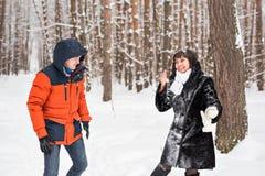 Lotta della palla di neve Coppie di inverno che hanno divertimento giocare in neve all'aperto Fotografie Stock