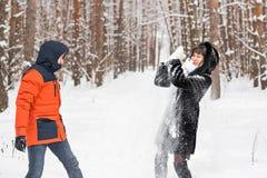 Lotta della palla di neve Coppie di inverno che hanno divertimento giocare in neve all'aperto Fotografia Stock