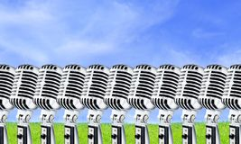 Lotta Mics-2. Open Air. Row Of Retro Mics Against Blue Sky And Green Grass Background (Design Element Stock Photo
