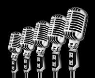 Lotta Mics. Row Of Retro Microphones Against Black Background Stock Photos
