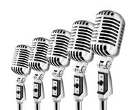 Lotta Mics. Row Of Retro Microphones Against White Background Stock Photography