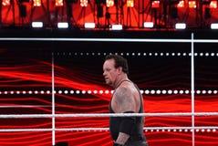 Lottatore di WWE gli sguardi fissi dell'impresario attraverso l'anello Immagini Stock