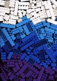 Lotten av cyan, blåa och purpurfärgade Lego för vit, blockerar bakgrund Arkivbild