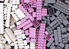 Lotten av rosa färger, grå färger och vit Lego blockerar bakgrund Fotografering för Bildbyråer
