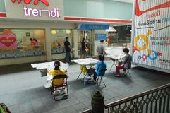 Lotterieeinzelhändler auf Bürgersteig am Einkaufsviertel in Bangkok Stockfotos