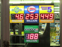 Lottery sign in NJ with jackpots shown . Powerball $188,000,000, Megamillion $253,000,000, Pick 6 Lotto $4,600,000 and other. Г. Gas station in NJ at night Stock Images