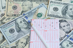 Lottery ticket and pencil on dollar background Stock Photo
