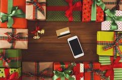 Lotti dei contenitori di regalo su fondo di legno con il telefono e la carta di credito Fotografie Stock Libere da Diritti