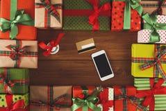 Lotti dei contenitori di regalo su fondo di legno con il telefono e la carta di credito Immagini Stock