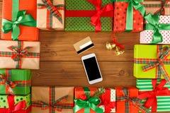 Lotti dei contenitori di regalo su fondo di legno con il telefono e la carta di credito nel centro, vista superiore, disposizione Fotografie Stock