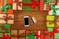Lotti dei contenitori di regalo su fondo di legno con il telefono e la carta di credito nel centro, vista superiore, disposizione Fotografia Stock