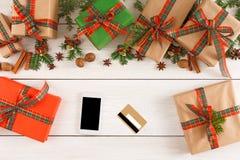Lotti dei contenitori di regalo su fondo di legno con il telefono e la carta di credito, vista superiore, disposizione piana Fotografia Stock