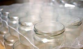 Lotti delle bottiglie di vetro per vari succhi ed inceppamenti Fotografia Stock
