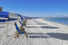 Lotti delle chaise-lounge del sole e degli ombrelli di spiaggia Fotografia Stock