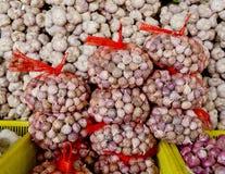Lotti delle lampadine italiane porpora bianche dell'aglio su esposizione da vendere a Fotografia Stock Libera da Diritti