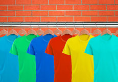 Lotti delle magliette sui ganci sopra il muro di mattoni arancio Fotografie Stock Libere da Diritti