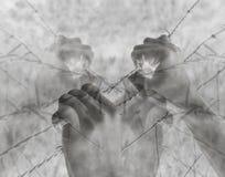 Lotti delle mani torturate che afferrano disperatamente filo spinato sul nero Fotografie Stock Libere da Diritti