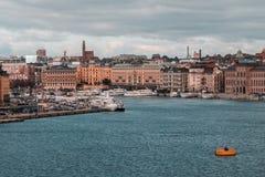 Lotti di più piccole barche ai pilastri in mezzo alla città, circondati con le vecchie costruzioni fotografia stock libera da diritti